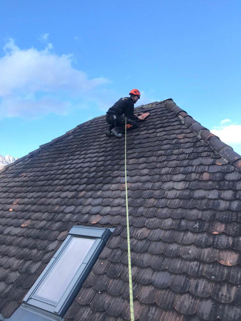 Dachdecker der Gantenbein Holzbau AG repariert Ziegel auf Hausdach in der Schweiz.